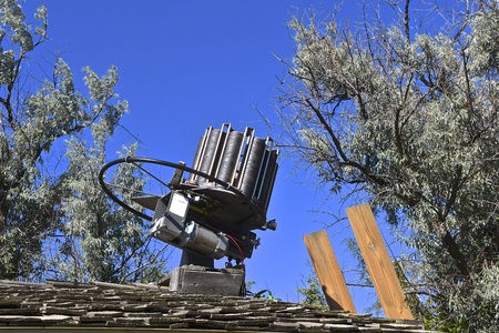 assimilate: An automatic clay pigeon thrower is anchored to the roof of a garage