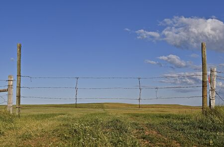 Barren hilly prairie pasture ranch land lies beyond a wire gate Stock Photo