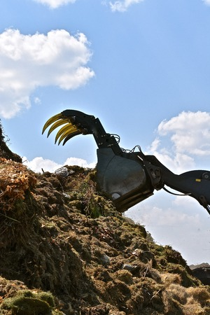 The sharp teeth of a front end loader lifts huge amounts of grass trimmings unto a compost pile, Stock Photo