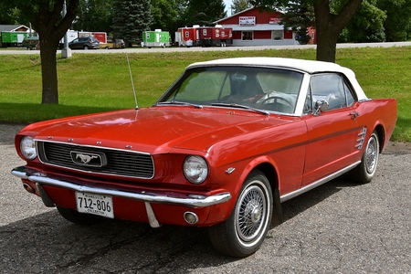 BATTLE LAKE, MINNESOTA, August 5, 2017: The red 1966 Ford mustang is a product of the Ford Motor Company located in Dearborn, Michigan started by Henry Ford and incorporated on June 16, 1903.