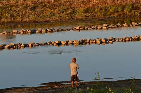An unidentified boy is fishing in a homemade drainage diversion canal.