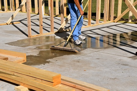 The  cement floor of a construction building site is being swept to remove a water puddle after a rain shower