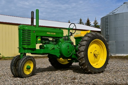 WOLVERTON, MINNESOTA, August 14, 2017: The classic restored G John Deere tractor is a product of John Deere Co, an American corporation that manufactures agricultural, construction, forestry machinery, diesel engines, and drive trains