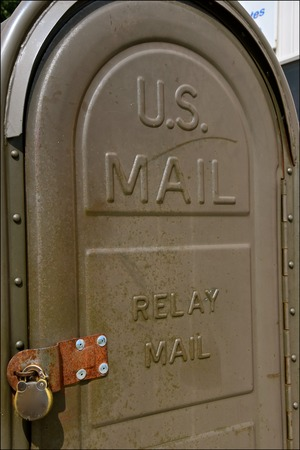 An old vintage  padlocked relay mail box is positioned in front of a small town post office. Stock Photo