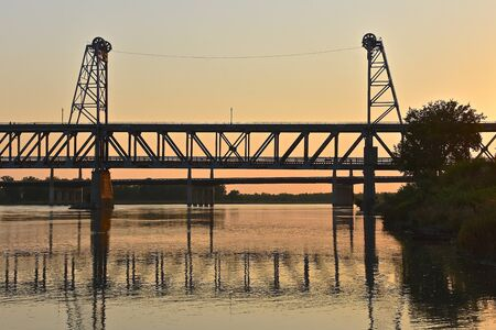 nebraska: A closed two tiered bridge of Yankton SD is reflected and silhouetted where it spans the Missouri River from Nebraska to South Dakota.