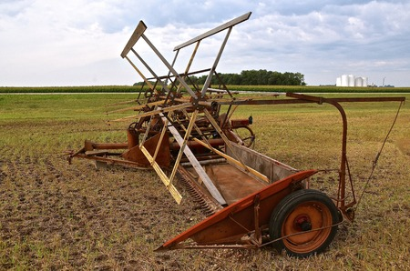 sickle: An old pull type  swather with no cab  and a wooden wheel iis parked in a field of wheat stubble. Stock Photo
