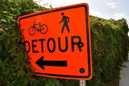 A detour sign leads bikers and pedestrians into the bushes Banco de Imagens