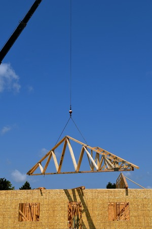 A boom and cable transfer a load of pre-made rafter to the top of a building under construction. Stock Photo - 84997622
