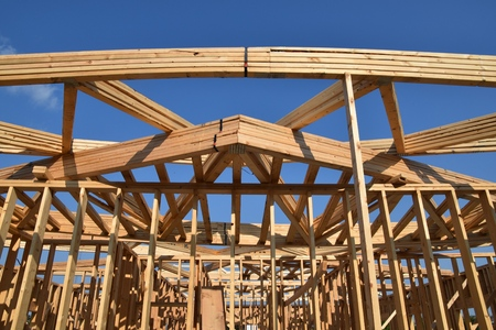 rafters: A load of pre-made rafters lie on the beams of a building under construction.