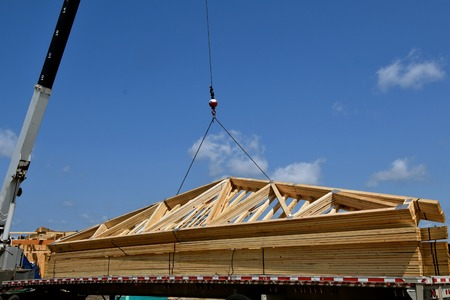 rafters: A boom and cable transfer a load of pre-made rafters(trusses) to the top of a building under construction.