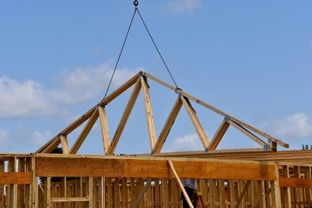 ブームとケーブルは、建設中のビルの上に既製の rafters(trusses) の負荷を転送します。 写真素材