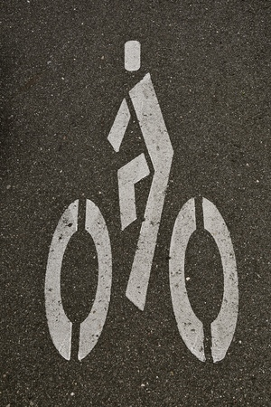 White painted bike lane symbol and sign on black asphalt Banco de Imagens