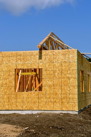 A lone truss is raced on the frame of a wooden building under construction. Stock Photo