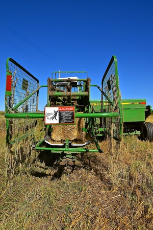 OSAKIS, MINNESOTA , September 8, 2017:  The bale thrower and cage parked in the stubble of a wheat field are  products of John Deere Co, an American corporation that manufactures agricultural, construction, forestry machinery, diesel engines, and drive tr