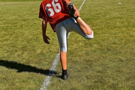 A young football player stretches leg muscles prior to practice.