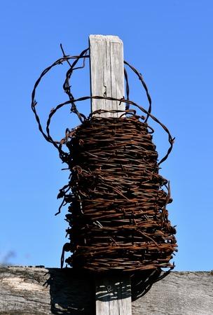 오래 된 녹슨 철 롤 롤 풍 화 오래 된 울타리 게시물 주위 포장입니다.