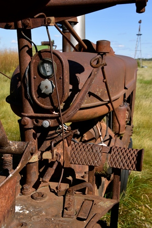 The electric box, gear shift lever, engine mounting,  and foot brake pedals  of an old rusty tractor Фото со стока