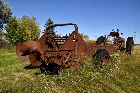 Een oude mestverspreider en een tractor worden vergeten in het lange gras Stockfoto