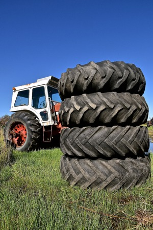 A pile of huge stacked tractor tires partially hides a tractor with a cab. Stock Photo