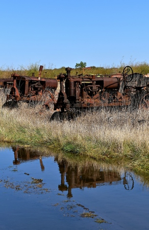 traction engine: Reflections of several old tractors in a salvage and junkyard are reflected in a pool of water.