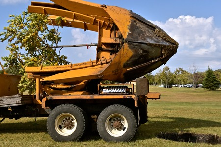 The mounted spade, jaws, and bucket are part of a tree removal machine  which removes and transplant young trees with their root system. Archivio Fotografico