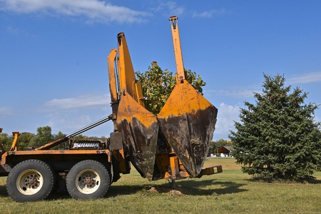 The mounted spade, jaws, and bucket are part of a tree removal and transplanting machine dropping the tree into the hole 스톡 콘텐츠