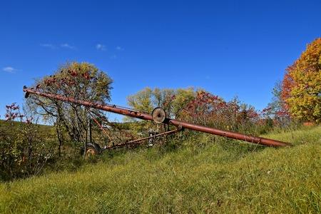 polea: An old rusty tube grain elevator is left in an autumn colored grove. Foto de archivo