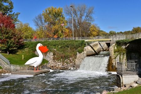 A huge replica of a white pelican is perched by a spillway from a dam