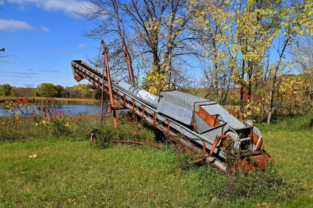 An old grain elevator with a folded back hopper is left in the long grass and  autumn colored leaves.
