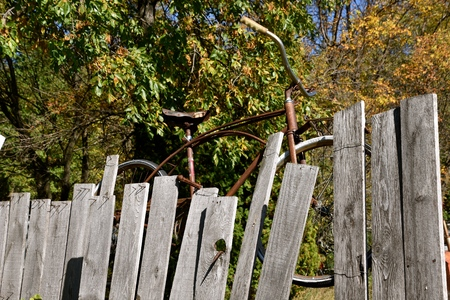 An old bicycle is hanging on a fence of gray weathered wood Banco de Imagens
