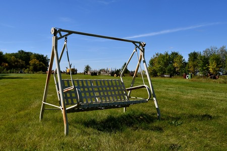 Comfortable outdoor swinging chair for two in a pasture with trucks and tractors in the background Stock fotó