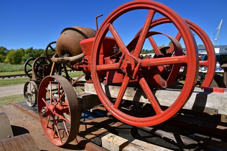 Red painted huge fly wheel of a gas engine which operated a cement mixer on wheels