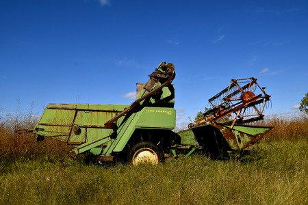 DOWNER, MINNESOTA, Oct 3, 2017: The old pull-type combine John Deer 42 combine is a product of John Deere Co, an American corporation that manufactures agricultural, construction, forestry machinery, diesel engines, and drivetrains
