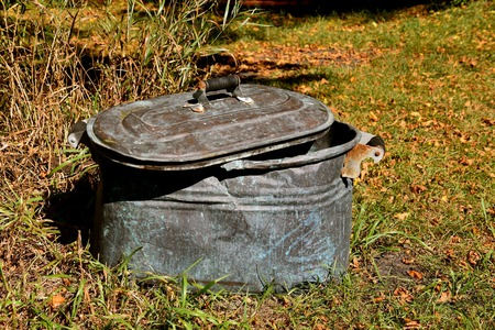 An old partially crumpled copper boiler with a lid and original wood handle 版權商用圖片