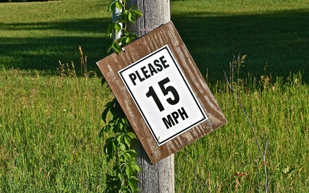 Crooked home owner signs asking traffic to drive slow