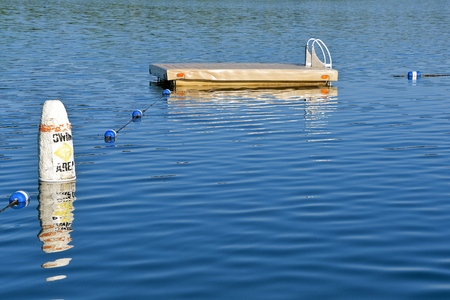 Swimming area on a lake is marked with buoys and a raft