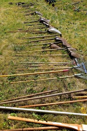 Een rij oude schoppen, schoppen, vorken, schoppen, harken en gatengravers met houten handvatten om te worden verkocht op een veiling. Stockfoto - 90060303