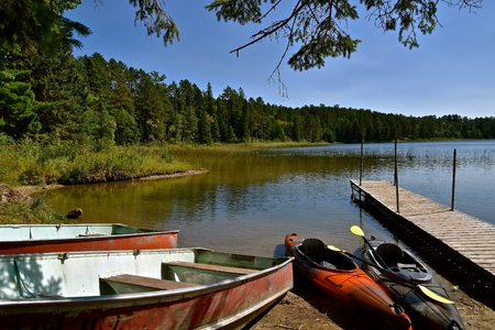 Row boats and canoes are left on a sandy beach near a dock in  a wooded area Stock Photo