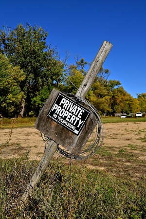 A crooked Private Property sign on a post identifies boundaries of land.