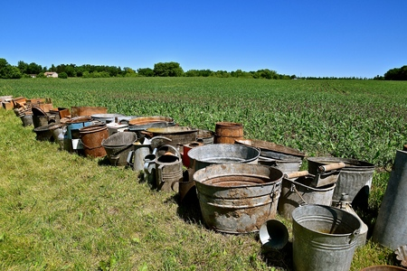 A row of old cans, pots, containers, and bushel baskets are in the grass to be sold at an auction