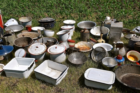 A collection of old household pots, pans, strainers, and pails displayed on the ground at an auction.