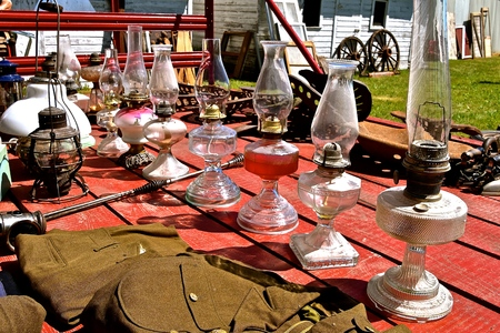 Antique kerosene lanterns are displayed on a table for an auction