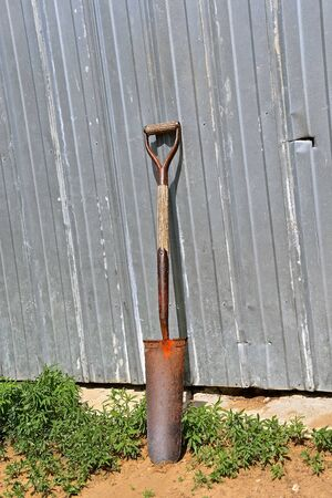 An old wood handled spade for digging deep narrow holes leans against a metal sided building. Stock Photo