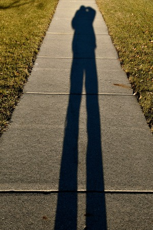 A photographer creates a  long shadowed selfie on the sidewalk with the late autumn sun low in the west.