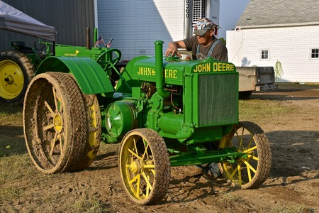 ROLLAG, MINNESOTA, Sept 1,  2017:  A restored John Deere D tractor is being filled with gasoline by the unidentified owner at the annual WCSTR farm show in Rollag held each Labor Day weekend where 1000s attend.