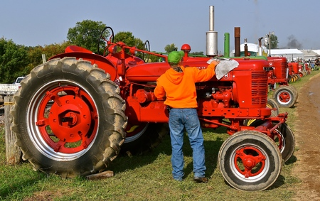 ROLLAG, MINNESOTA, Sept 1, 2017: An unidentified man polished a restored H Farmall tractor displayed at the annual WCSTR farm show in Rollag held each Labor Day weekend where 1000s attend.