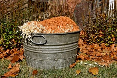 古い金属のブッシェルバスケットは、木材を切断からおがくずをロードされています 写真素材 - 92529002