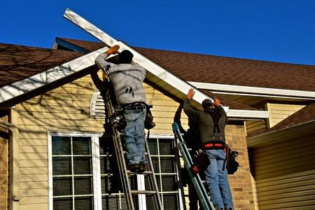 Numerosi operai edili non identificati stanno sostituendo la facia su una casa di acciaio.