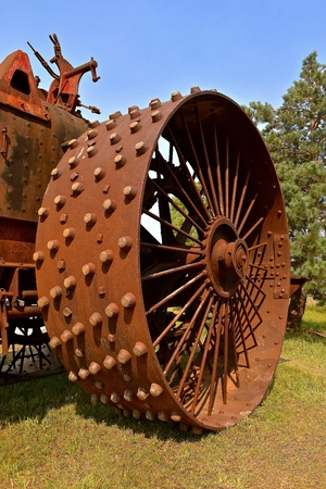 A massive huge metal and rusty iron wheel of an old steam engine Stock Photo