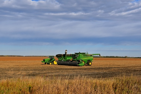 HALSTAD, MINNESOTA: October 7,2017:  The John Deere tractor and combine parked in partially harvested soybean field  are products of John Deere Co, an American corporation that manufactures agricultural, construction, forestry machinery, diesel engines,,  Editorial